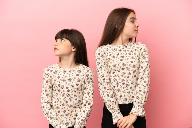 Маленькие сестры девочки, изолированные на розовом фоне нервничают и испуганы