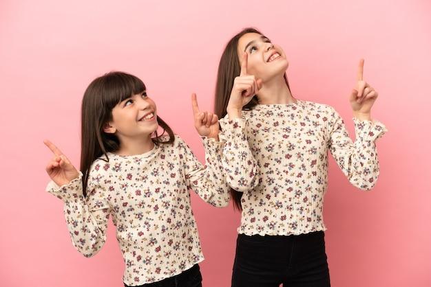 검지 손가락으로 가리키는 분홍색 배경에 격리된 어린 자매 소녀들