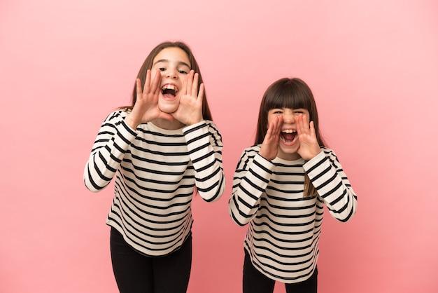 Маленькие сестрички, изолированные на розовом фоне, кричат и что-то объявляют