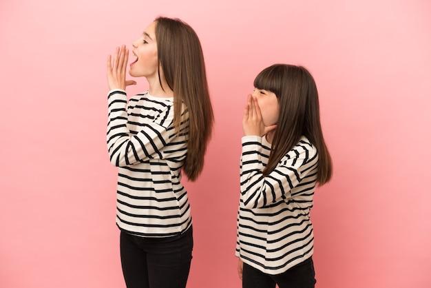 ピンクの背景に孤立した妹の女の子は、横に大きく開いた口で叫んでいます