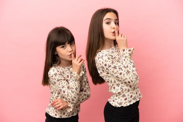 Маленькие сестры девочки изолированы на розовом фоне, показывая знак закрывающегося рта и жест молчания