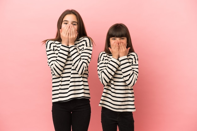 ピンクの背景に孤立した妹の女の子は口を覆っている間たくさん笑っています