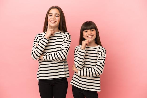 Маленькие сестры девочки изолированы на розовом фоне, улыбаясь сладким выражением лица