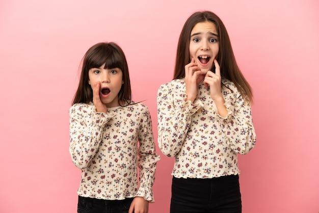 ピンクの背景に孤立した妹の女の子は、右を見ながら驚いてショックを受けました