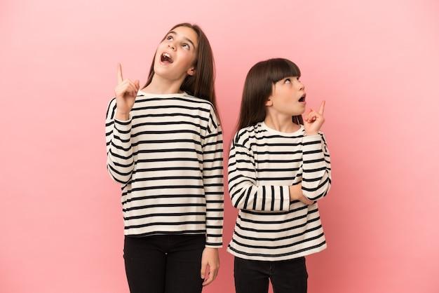 Маленькие сестры девочки изолированы на розовом фоне, думая об идее, указывая пальцем вверх