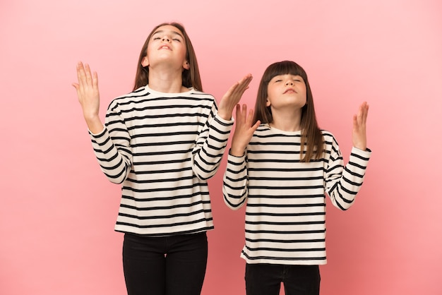 Little sisters girls isolated on pink background frustrated by a bad situation