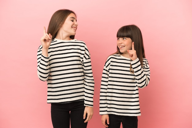 Little sisters girls isolated on pink background intending to realizes the solution while lifting a finger up