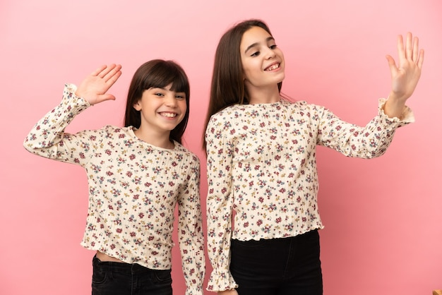 Little sisters girls isolated on pink background saluting with hand with happy expression