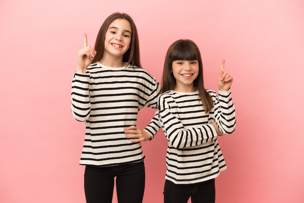 Little sisters girls isolated on pink background showing and lifting a finger in sign of the best