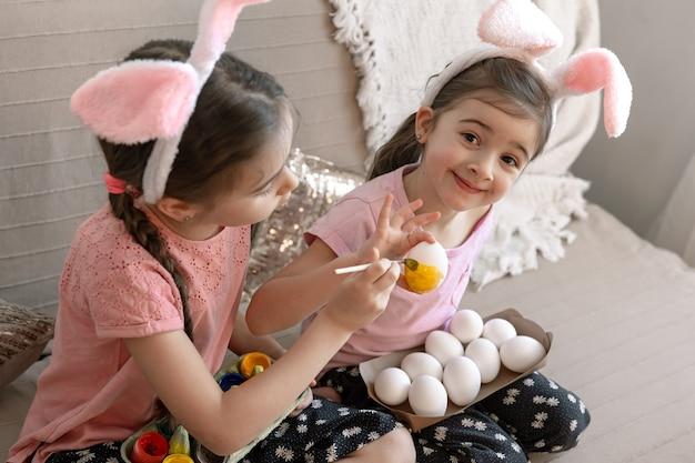 Сестрички в кроличьих ушках раскрашивают пасхальные яйца на диване дома
