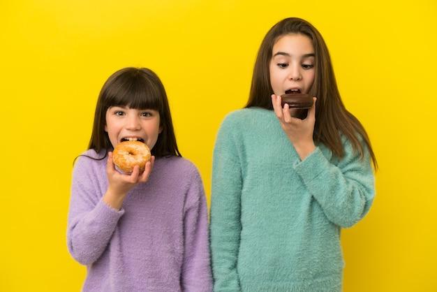 Маленькие сестры, изолированные на желтом фоне, едят пончик