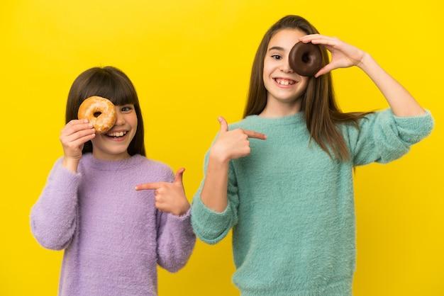 Маленькие сестры, изолированные на желтом фоне, держат пончик и счастливы