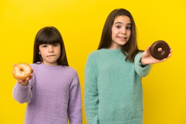 Маленькие сестры изолированы на желтом фоне, держа пончик и грустно