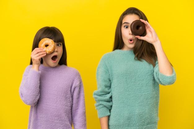 Маленькие сестры, изолированные на желтом фоне, держа в глазу пончик