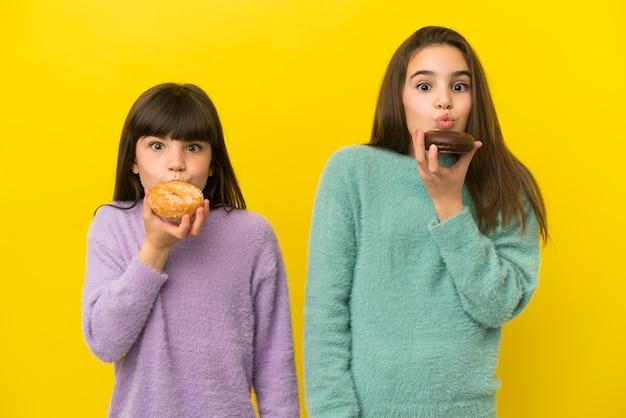Маленькие сестры, изолированные на желтом фоне, держа пончик