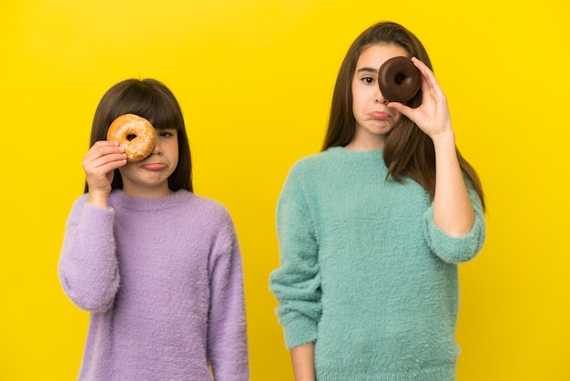 Маленькие сестры изолированы на желтом фоне, держа пончики в глазах с грустным выражением лица Premium Фотографии