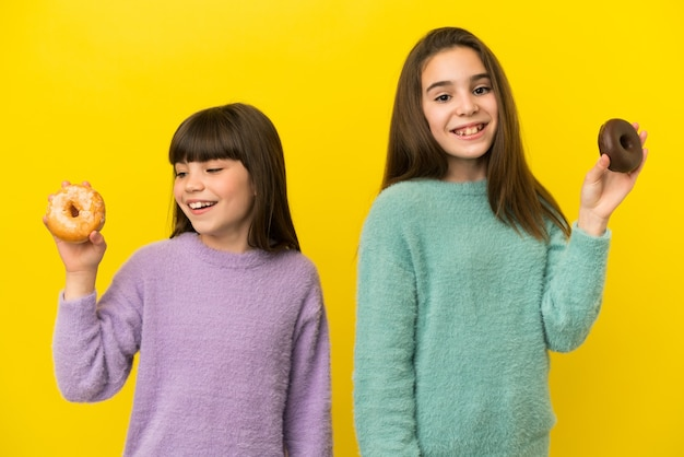 Маленькие сестры, изолированные на желтом фоне, держат пончики со счастливым выражением лица