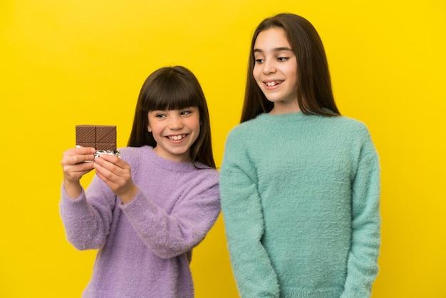 Маленькие сестры изолированы на желтом фоне, принимая шоколадную таблетку и счастливы