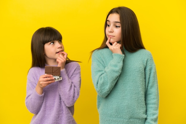 Маленькие сестры изолированы на желтом фоне, принимая шоколадную таблетку и сомневаясь