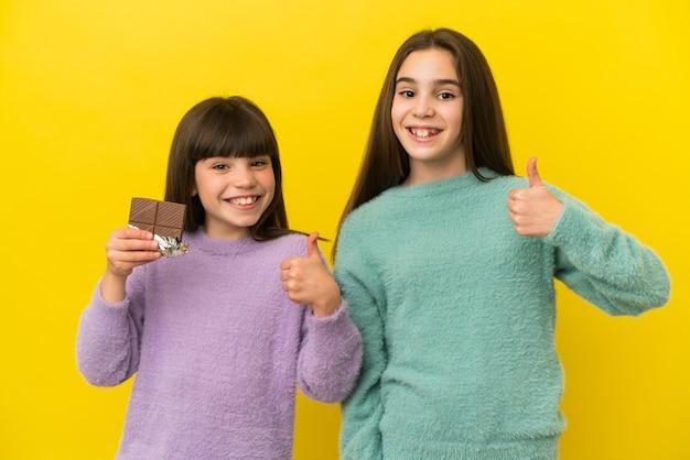 チョコレートのタブレットを取り、親指を立てて黄色の背景に分離された妹