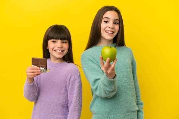 한 손에는 초콜릿 태블릿을 다른 한 손에는 사과를 복용하는 노란색 배경에 고립 된 작은 자매