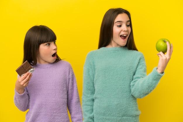 한 손에는 초콜릿 태블릿을, 다른 한 손에는 사과를 복용하는 여동생