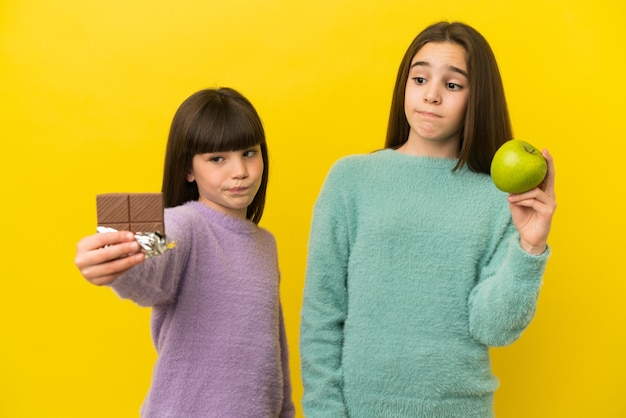 Little sisters isolated on yellow background having doubts while taking a chocolate tablet in one hand and an apple in the other