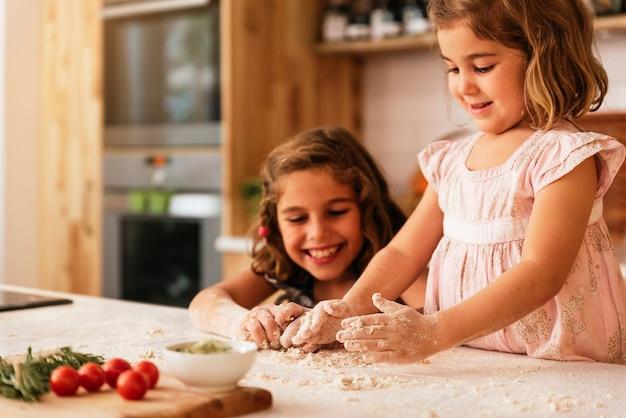 Маленькие сестры замешивают тесто, готовясь к выпечке печенья. концепция младенческого шеф-повара.