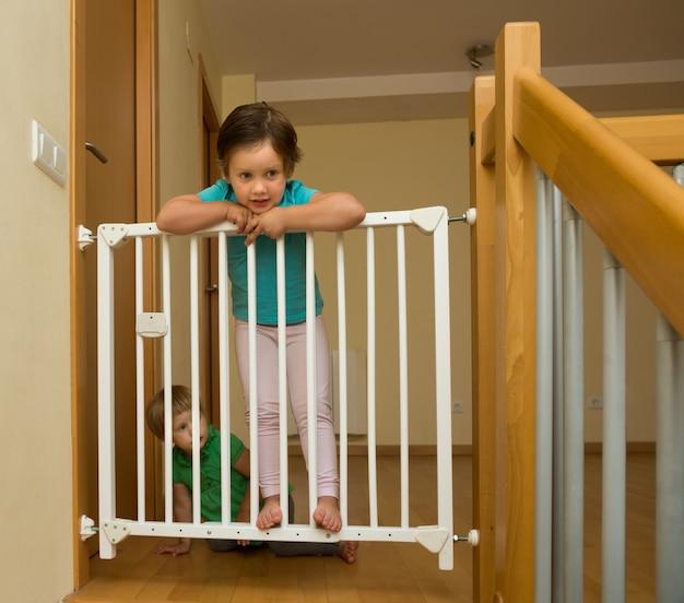 Little sisters near stair gate