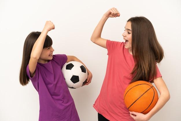Маленькие сестры, играющие в футбол и баскетбол, изолированные на белом фоне, празднуют победу в позиции победителя