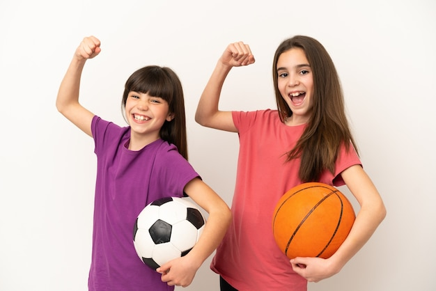 Маленькие сестры, играющие в футбол и баскетбол, изолированные на белом фоне, празднуют победу