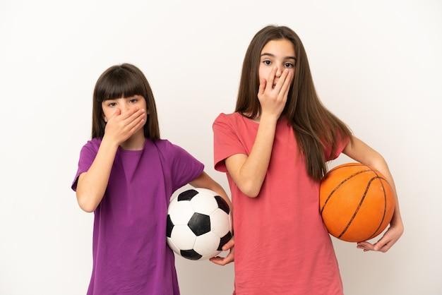 Маленькие сестры играют в футбол и баскетбол на белом фоне, прикрывая рот руками за то, что говорят что-то неуместное