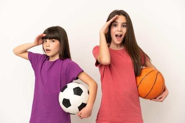 흰색 배경에 고립 된 축구와 농구를하는 여동생은 방금 뭔가를 깨달았으며 해결책을 계획하고 있습니다.