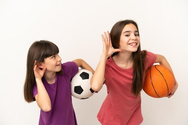 Маленькие сестры играют в футбол и баскетбол на белом фоне, слушая что-то, положив руку на ухо