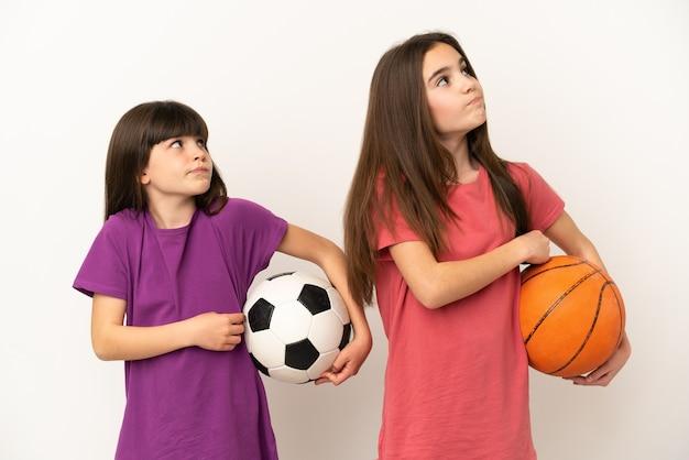 축구와 농구를하는 여동생은 어깨를 들어 올리는 동안 의심 제스처를 만드는 흰색 배경에 고립