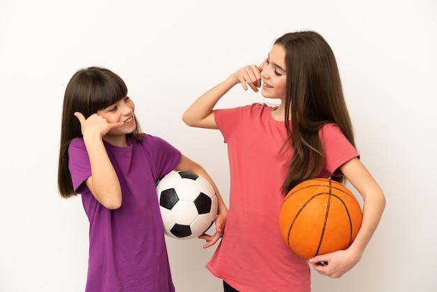 Маленькие сестры, играющие в футбол и баскетбол, изолированные на белом фоне, делая жест телефона. перезвони мне знак