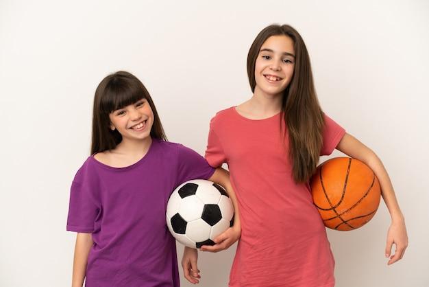 Маленькие сестры играют в футбол и баскетбол, изолированные на белом фоне, позируют с руками на бедрах и улыбаются