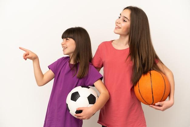 축구와 농구를하는 여동생을 향해 웃고있는 동안 아이디어를 제시하는 흰색 배경에 고립