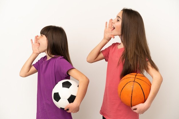 축구와 농구를하는 여동생은 측면에 입 벌리고 외치는 흰색 배경에 고립
