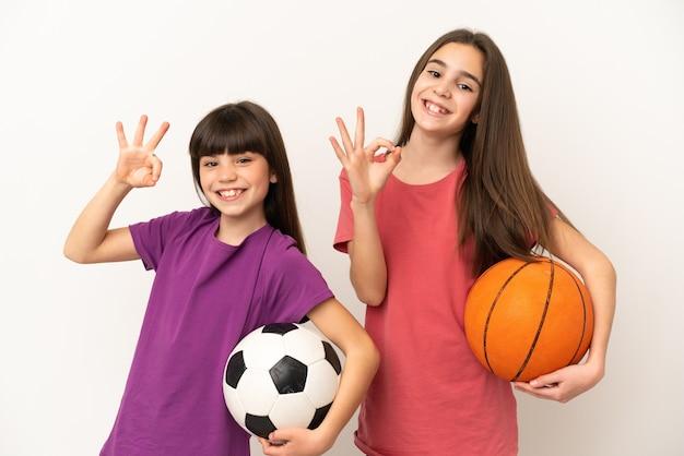손가락으로 확인 표시를 보여주는 흰색 배경에 고립 된 축구와 농구를하는 여동생