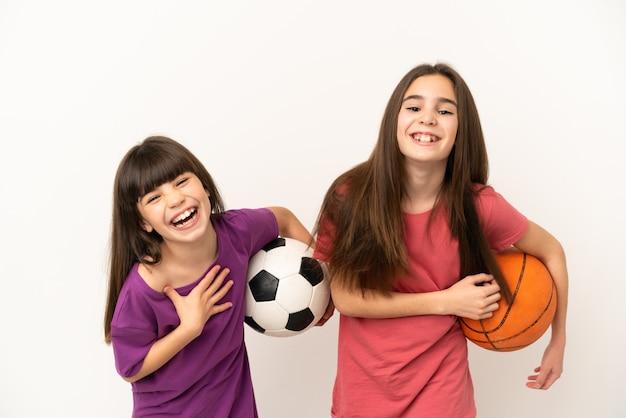 Маленькие сестры, играющие в футбол и баскетбол, изолированные на белом фоне, много улыбаются, кладя руки на грудь