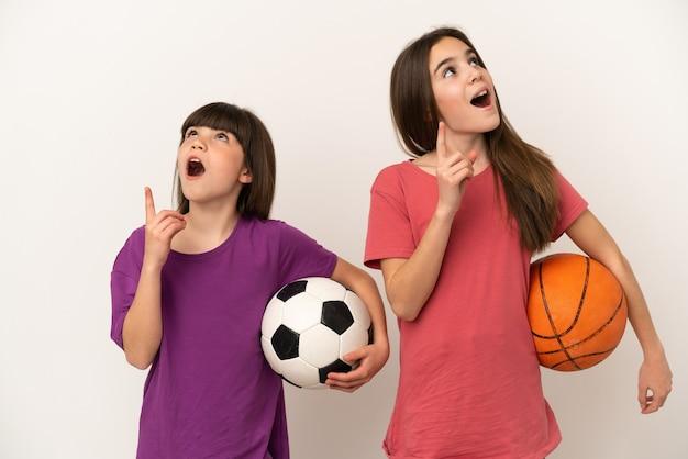 축구와 농구를하는 작은 자매는 손가락을 가리키는 아이디어를 생각하는 흰색 배경에 고립