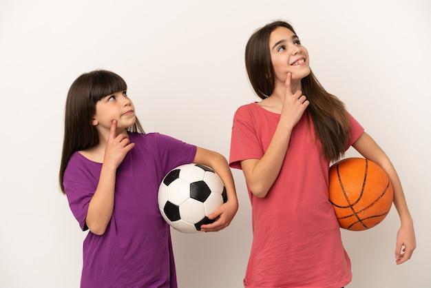 Маленькие сестры играют в футбол и баскетбол на белом фоне, думая об идее, глядя вверх
