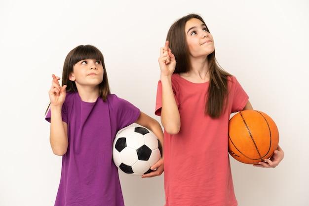 축구와 농구를하는 여동생은 손가락을 건너고 최고를 바라는 흰색 배경에 고립