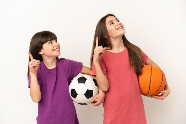 축구와 농구를하는 여동생은 검지 손가락으로 좋은 아이디어를 가리키는 격리
