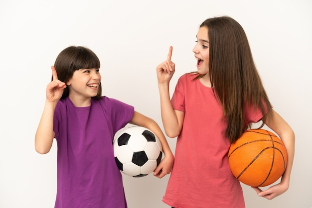 Little sisters playing football and basketball isolated intending to realizes the solution while lifting a finger up