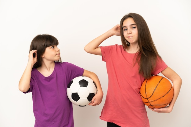 Little sisters playing football and basketball isolated on white background having doubts while scratching head