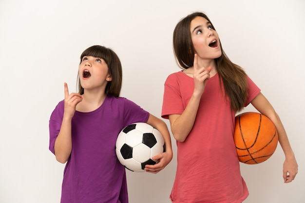 Little sisters playing football and basketball isolated on white background thinking an idea pointing the finger up