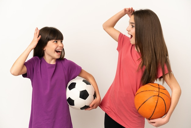 Little sisters playing football and basketball isolated on white background with surprise and shocked facial expression