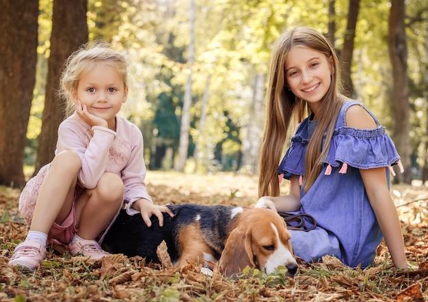 Маленькие сестры играют с собакой в парке осенью